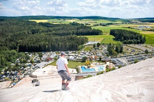 Ein Paradies für Adrenalin-Junkies: Auf dem weißen Quarzsand des imposanten Monte Kaolinos fahren Boarder, Biker oder Sandskifahrer auch in der Sommersaison rasant dem Tal entgegen. (Foto: epr/Freizeitpark Monte Kaolino)