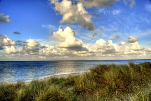 Wasser, Wolken und Dünen lassen sich bei einem Sylt-Urlaub zu beeindruckenden Fotos komponieren. Hobbyfotografen können ihre besten Aufnahmen anschließend anderen Fans der Nordseeinsel präsentieren. Foto: djd/Kurverwaltung List/M.Koch