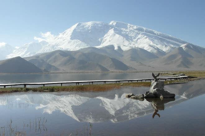 Akklimatisations-Trekking am Fuße des Eisriesen Muztagh Ata, 7.546 Meter hoch, der sich hier schön im Kara Kul See spiegelt. Foto: djd/DAKS - die Welt der Berge