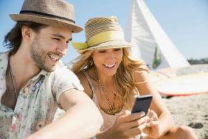 Neuigkeiten über Social Media verbreiten, die Lieblingsmusik per Streaming am Strand hören oder Videoclips schauen - das Smartphone ist auch im Urlaub stets griffbereit. Foto: djd/Telefónica/Corbis